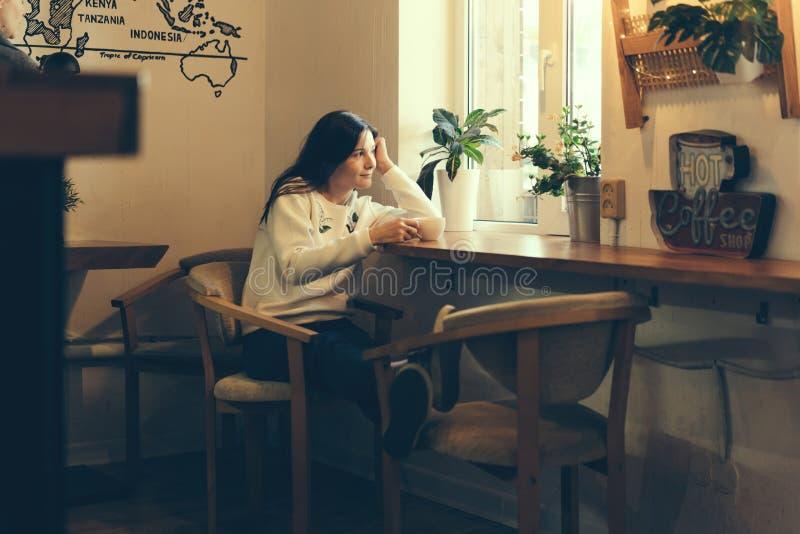 Fille dans un café par la fenêtre image stock