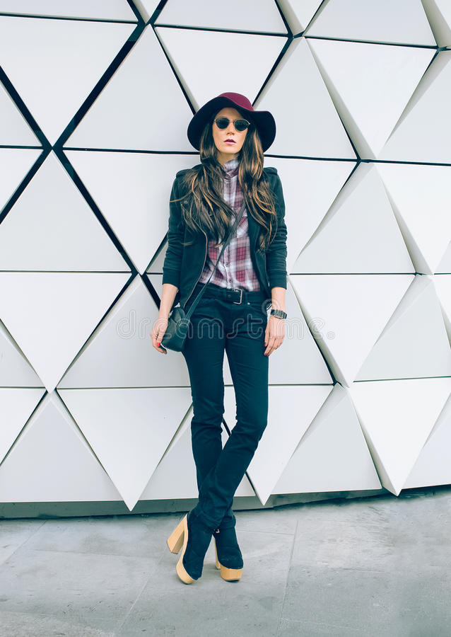 Fille dans un chapeau élégant sur une rue de ville Type de mode photos libres de droits