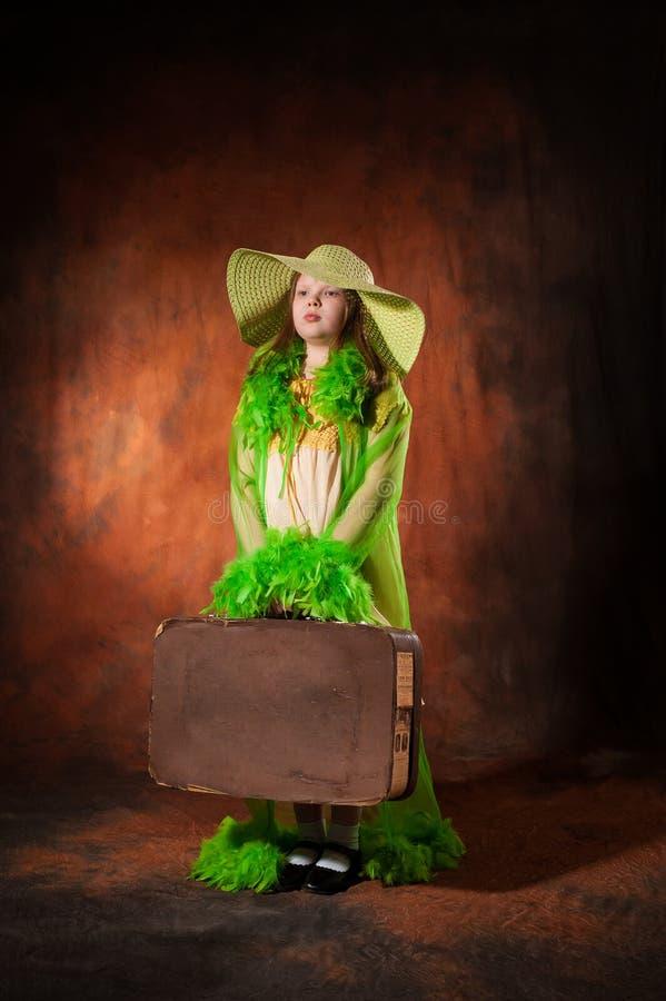 Fille dans un chapeau avec une vieille valise photos stock