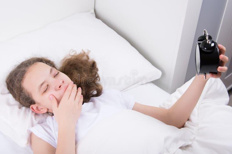 Fille dans un lit blanc, baîllement, tenant un réveil image libre de droits