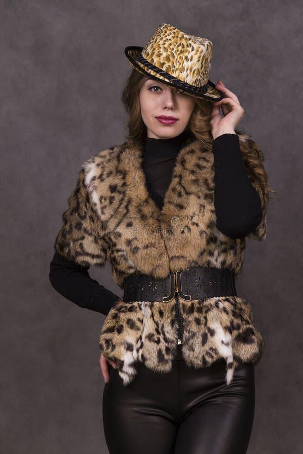 Fille dans un manteau de fourrure et un chapeau posant dans le studio images libres de droits