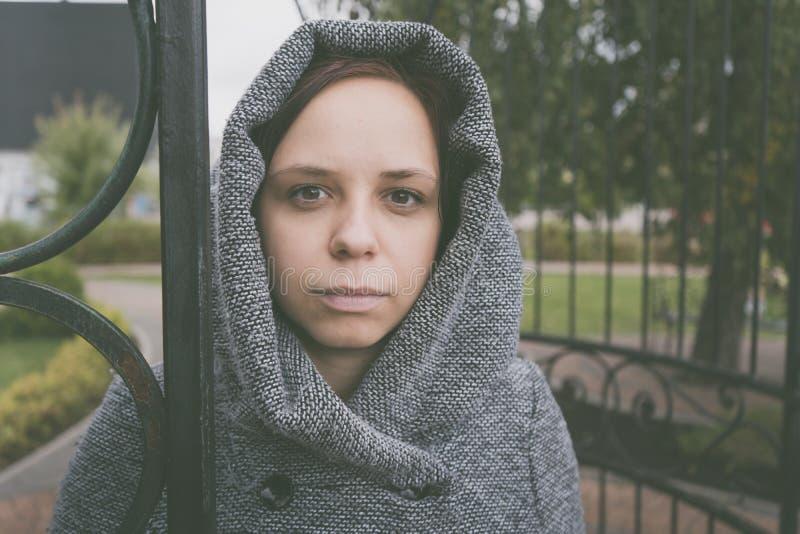 Fille dans un manteau posant dehors pendant l'automne par temps sombre, scrutant pensivement dans la distance le concept du depre image stock