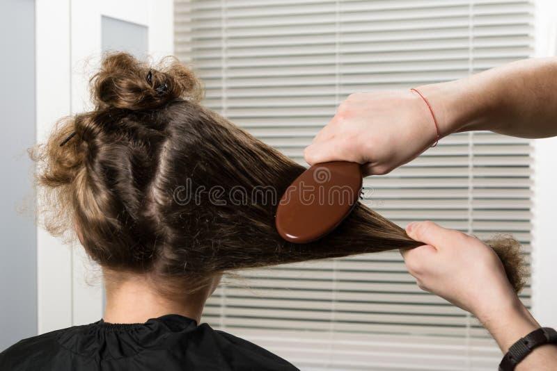Fille dans un salon de beauté, un styliste faisant une coiffure images stock