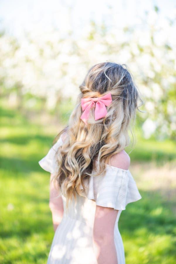 Fille dans un verger de floraison au printemps Concept de recherche ou de dissimulation R?tro robe de style Ressorts colorés photographie stock libre de droits