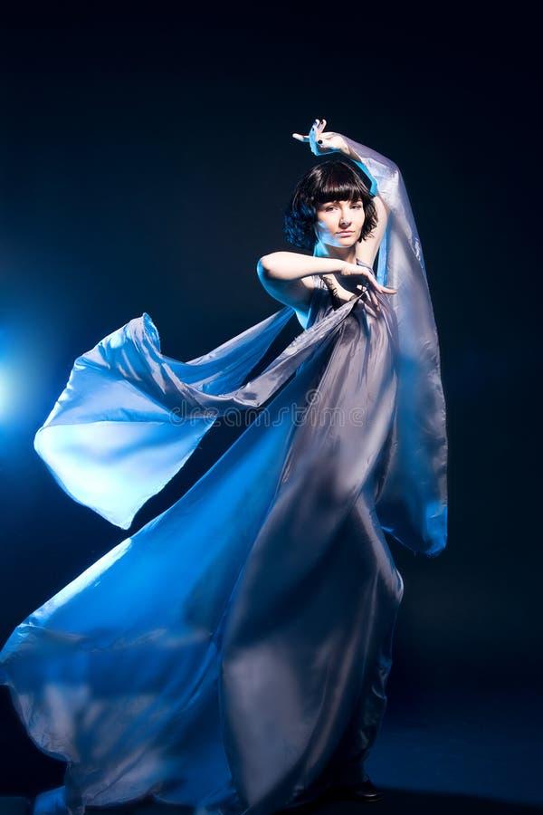 Fille dans un vol gris de robe avec le contre-jour bleu photos stock