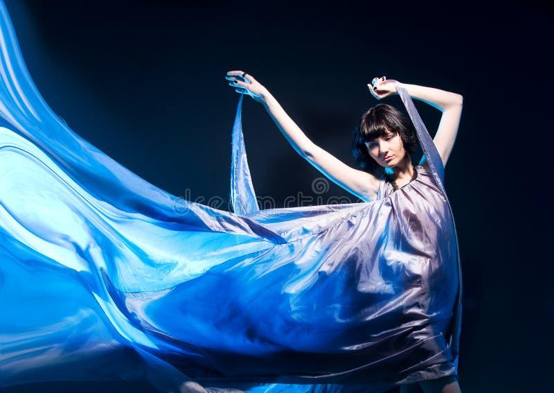 Fille dans un vol gris de robe avec le contre-jour bleu image stock