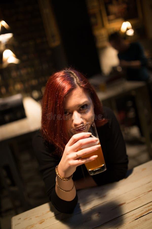 Fille dans une bière potable de métier de bar photos stock
