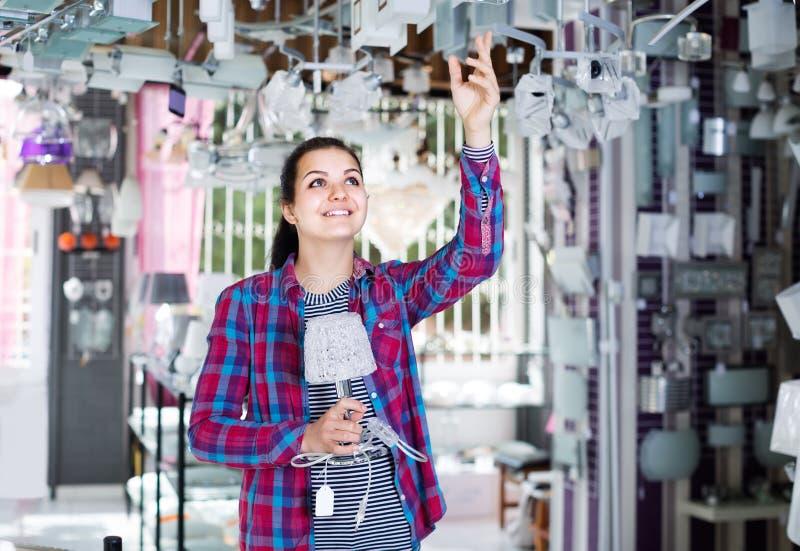Fille dans une boutique plus légère choisissant le lustre en verre moderne pour la maison photo libre de droits