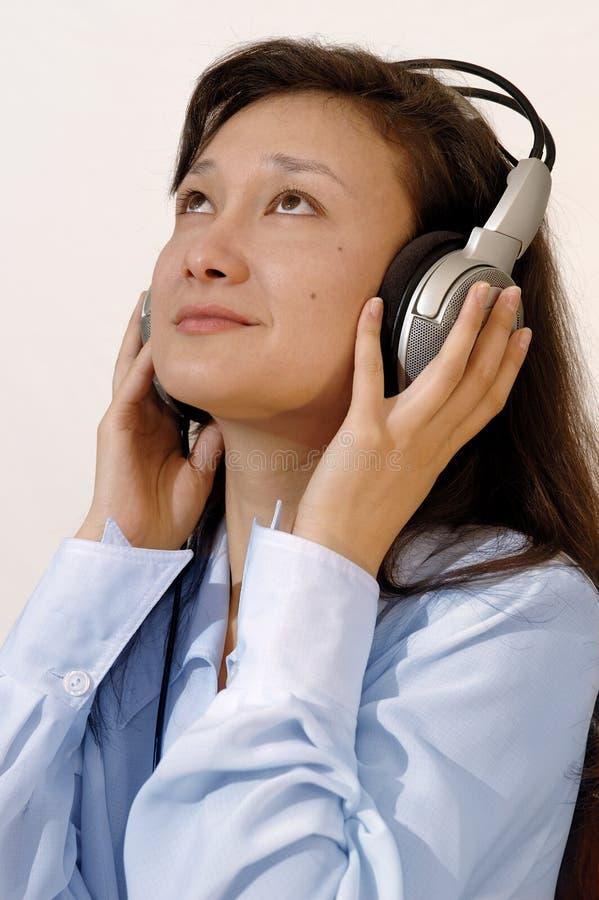 Fille dans une chemise bleue avec des écouteurs image libre de droits