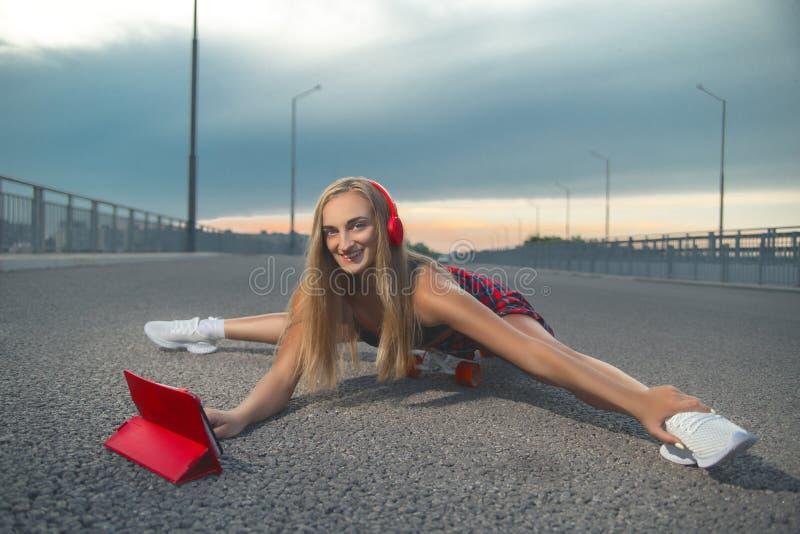 Fille dans une chemise rouge au coucher du soleil avec le patin et les écouteurs photo libre de droits