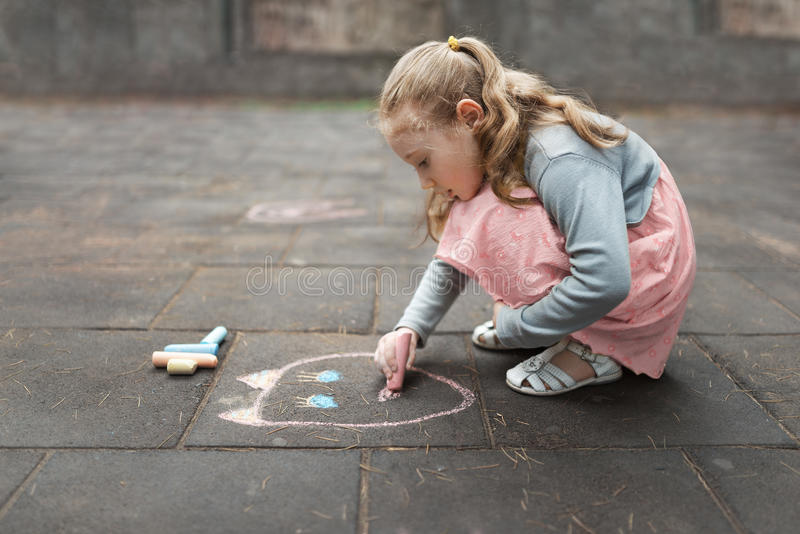 Fille dans une craie de dessin rose de robe sur le trottoir image stock