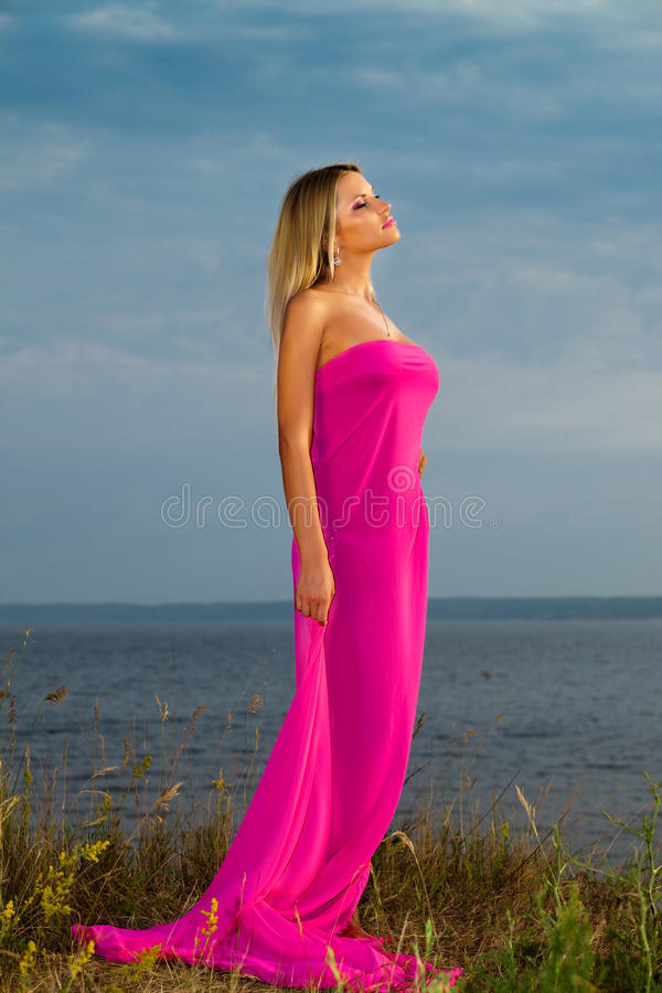 Fille dans une longue robe rose. image stock