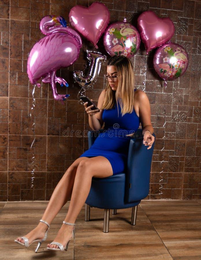 Fille dans une robe élégante courte bleue se reposant dans une chaise bleue et des utilisations un smartphone photos stock