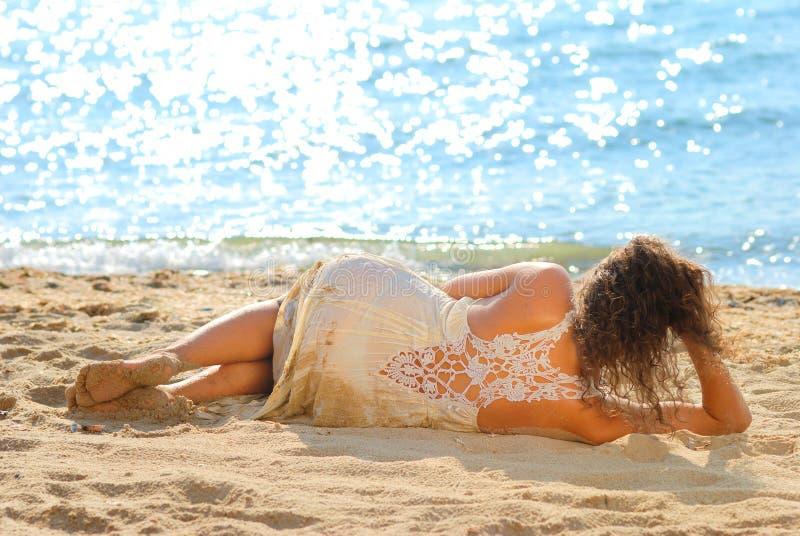 Fille dans une robe blanche s'étendant sur la plage photos stock