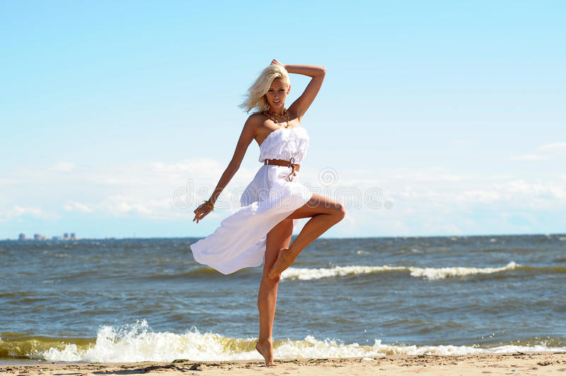 Fille dans une robe blanche sur la plage image stock