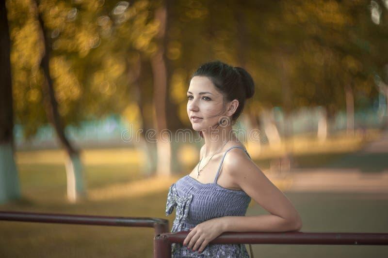 Fille dans une robe bleue en parc Fille dans une robe bleue en parc vert d'été photo stock