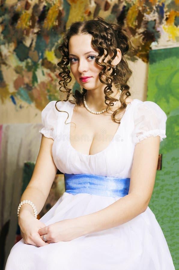 Fille dans une robe de boule historique, posant dans un studio photo stock