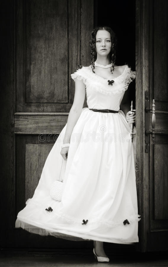 Fille dans une robe de vintage sortant des portes photo libre de droits