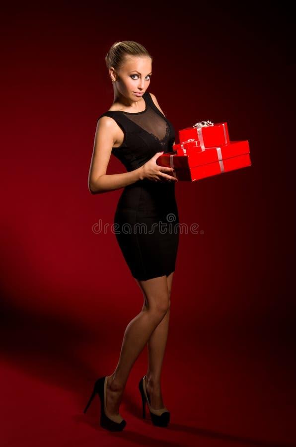Fille dans une robe noire avec des cadeaux dans des mains images libres de droits