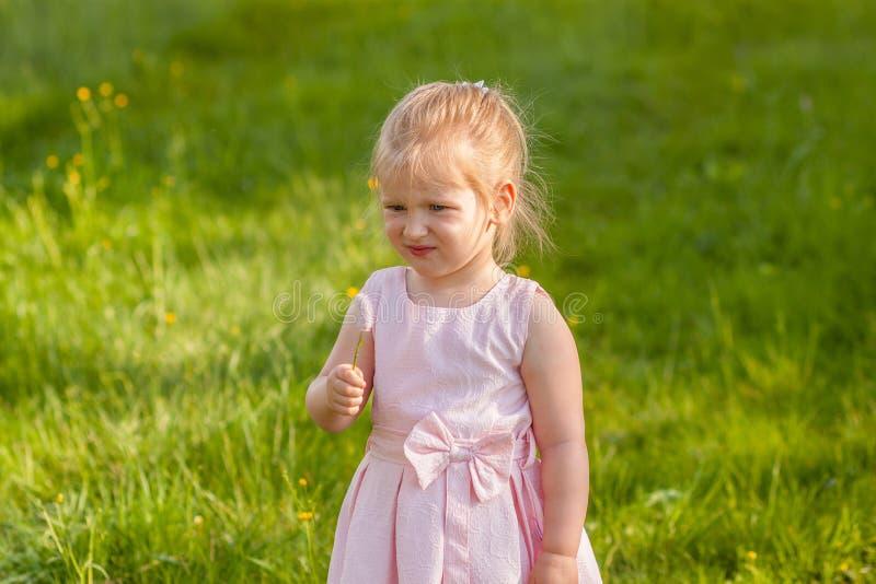 Fille dans une robe rose avec une fleur dans sa main images stock