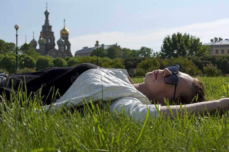 Fille dans une veste blanche et des lunettes de soleil se trouvant sur l'herbe sur images stock