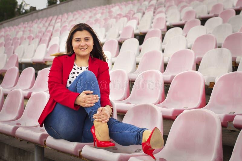 Fille dans une veste rouge sur les sièges de stade photographie stock libre de droits