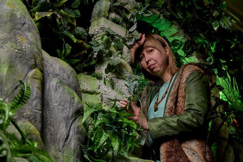 Fille dans une veste verte avec les cheveux blonds près d'une roche artificielle avec une grotte Séance photos fabuleuse dans le  photographie stock libre de droits