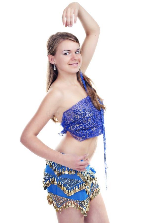 Fille dansant la danse orientale dans un procès bleu image stock