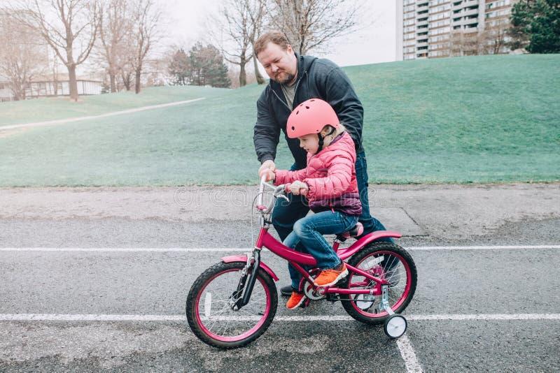 Fille de aide de fille de p?re de formation caucasienne de papa pour monter la bicyclette image libre de droits
