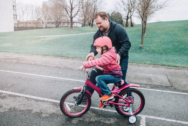 Fille de aide de fille de p?re de formation caucasienne de papa pour monter la bicyclette image stock