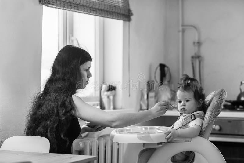 Fille de alimentation de jeune mère photographie stock libre de droits