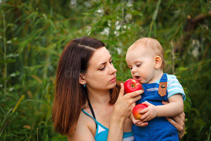 Fille de alimentation de mère avec des pommes photo stock