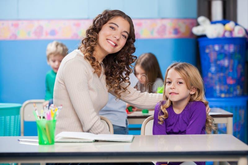 Fille de With Arm Around de professeur petite dans la salle de classe photos libres de droits