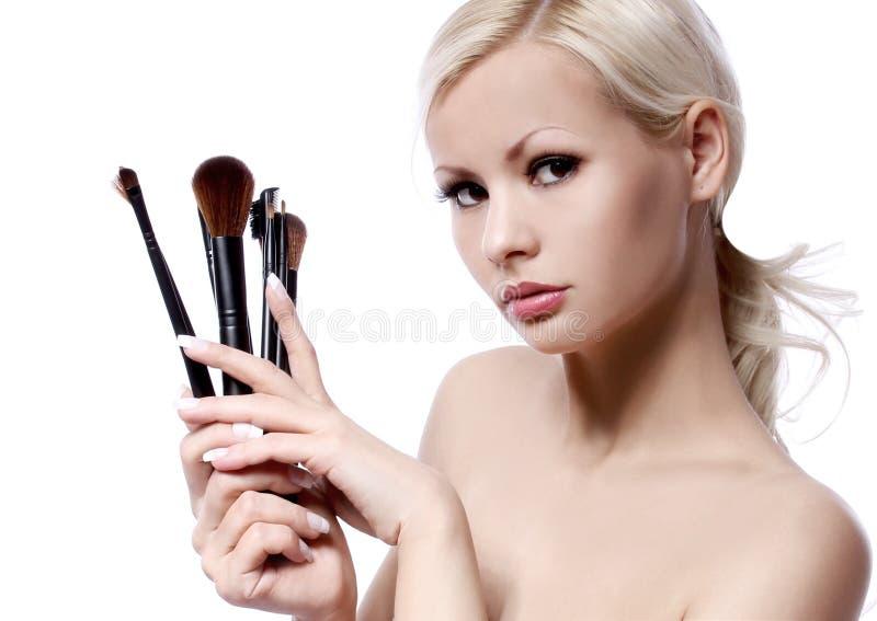 Fille de beauté avec des brosses de maquillage d'isolement sur le blanc. belle blonde photos libres de droits