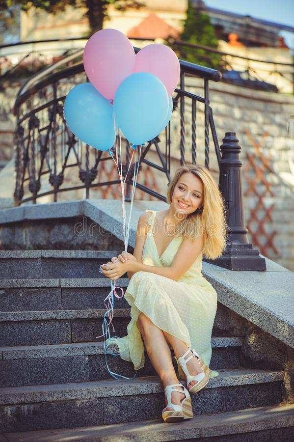 Fille de beauté avec les ballons colorés riant sur des étapes de ville Belle jeune femme heureuse un jour lumineux ensoleillé Mod photos stock