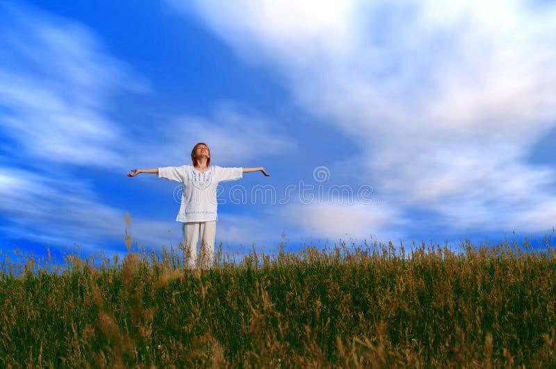 Fille de beauté dans le domaine sous des nuages photographie stock libre de droits
