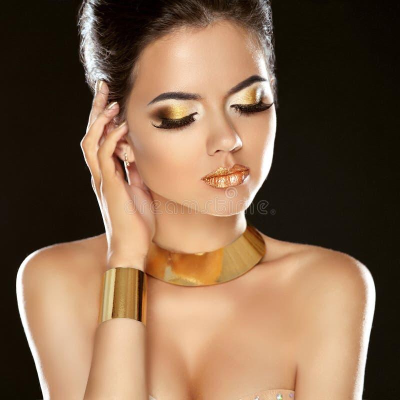 Fille de beauté de mode d'isolement sur le fond noir Bijoux d'or photo libre de droits
