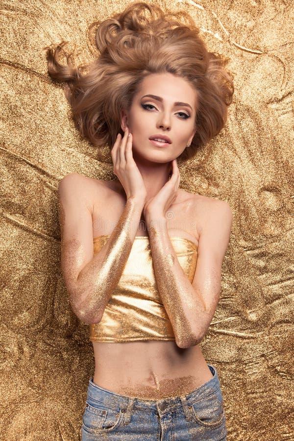 Fille de beauté de mode se trouvant sur le scintillement d'or photos stock