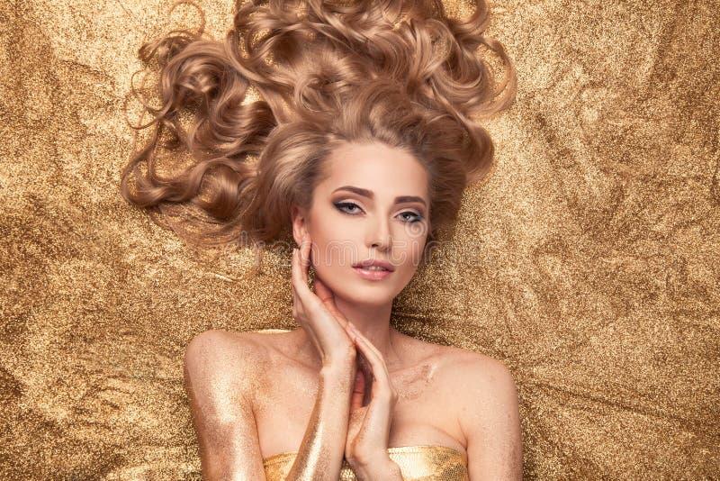 Fille de beauté de mode se trouvant sur le scintillement d'or images stock