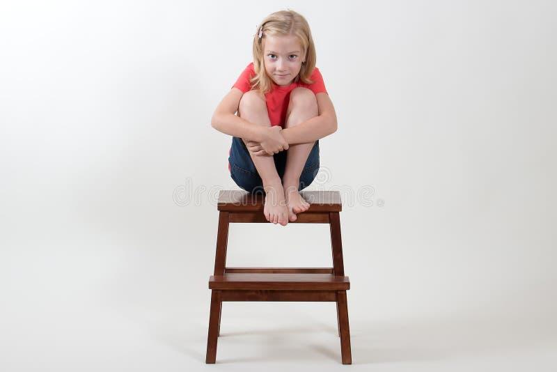 Fille de beauté s'asseyant sur un tabouret photos stock