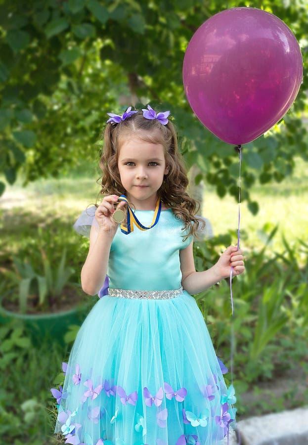 Fille de bel enfant dans la robe élégante avec le ballon de médaille et d'air d'or image libre de droits