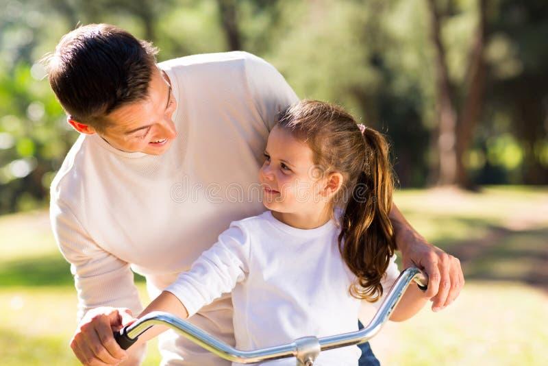 Fille de bicyclette de père photographie stock libre de droits