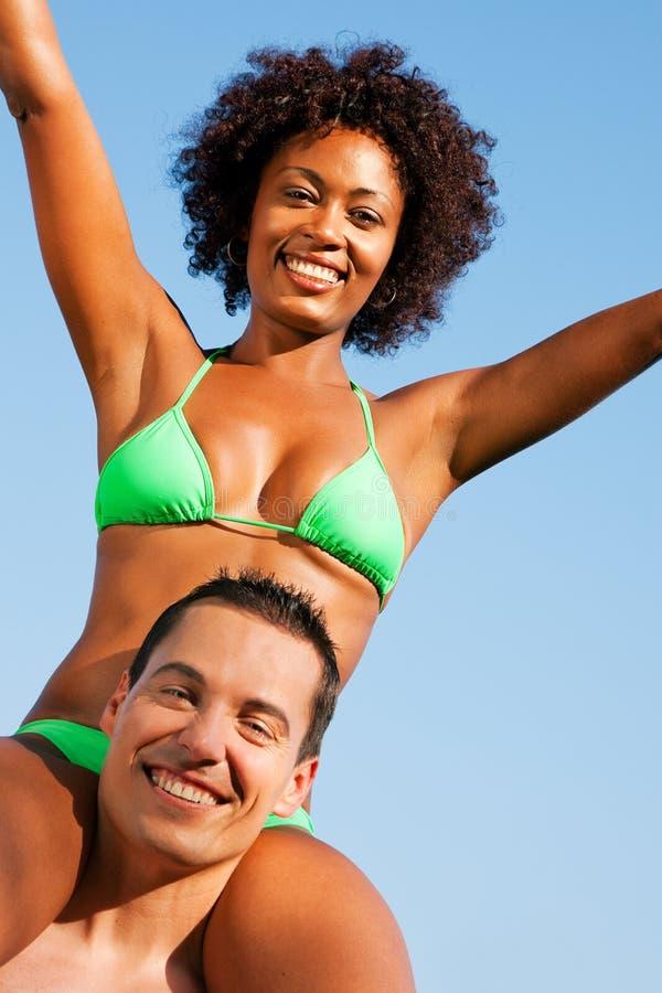 Fille de bikini d'été s'asseyant sur des épaules de l'homme photos stock