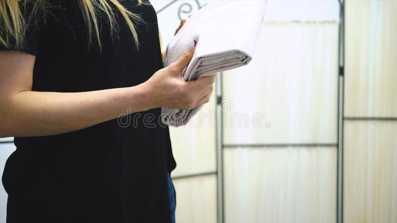 Fille de blanchisserie de travailleur tenant les serviettes fraîches dans des ses mains barre Femme tenant une serviette dans des photographie stock libre de droits