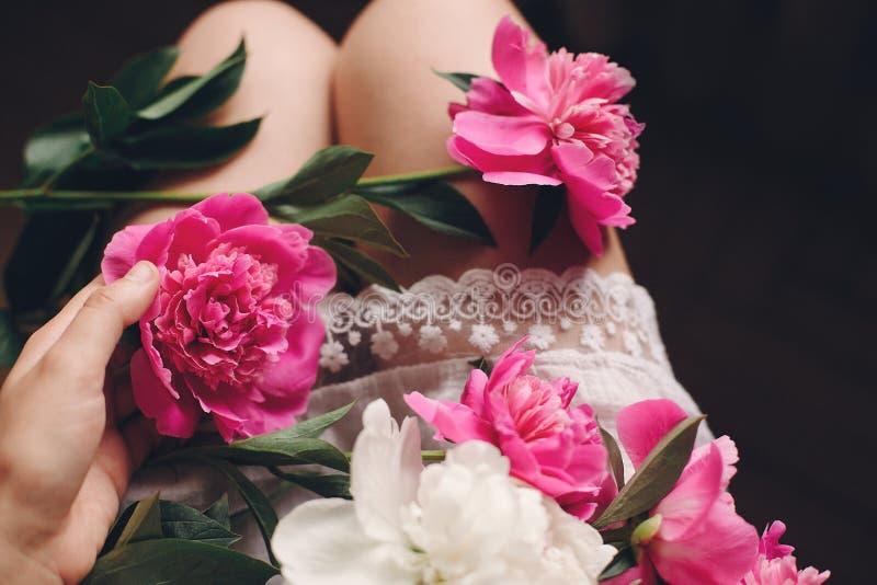 Fille de Boho dans la robe blanche de la Bohême tenant de belles pivoines roses sur des jambes, vue supérieure L'espace pour le t photo libre de droits