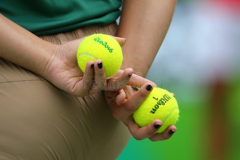 Fille de boule tenant la balle de tennis de Wilson pendant le match de Rio 2016 Jeux Olympiques au centre olympique de tennis image stock