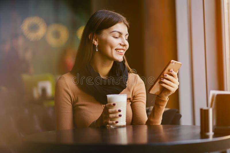 Fille de brune à l'aide du téléphone tandis qu'à un restaurant images libres de droits