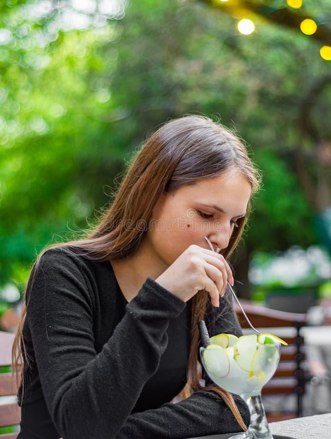 Fille de brune d'adolescent avec de longs cheveux mangeant la crème glacée en café extérieur image libre de droits