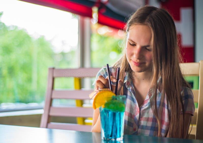 Fille de brune d'adolescent avec de longs cheveux tenant un verre avec un cocktail bleu de limonade avec des fruits à une table e image stock