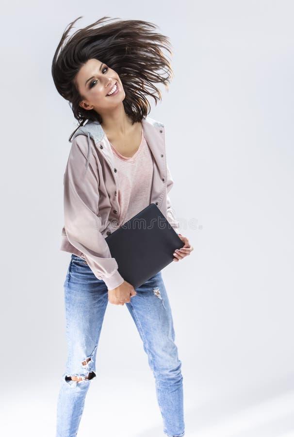 Fille de brune tenant l'ordinateur portable dans l'avant sur des mains dans les vêtements décontractés contre le blanc Fabricatio photos stock